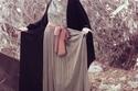عباءة من الحرير الاسود مع دانتيل فضي رمادي مبطن بقطعة قماش معدنية اللون،وحزام وردي على الخصر ينسدل اسفله حرير رمادي