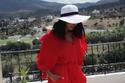تنسيقات مودل شادن للقوام الممتلئ: فستان حريري أحمر قصير مع بوت وقبعة